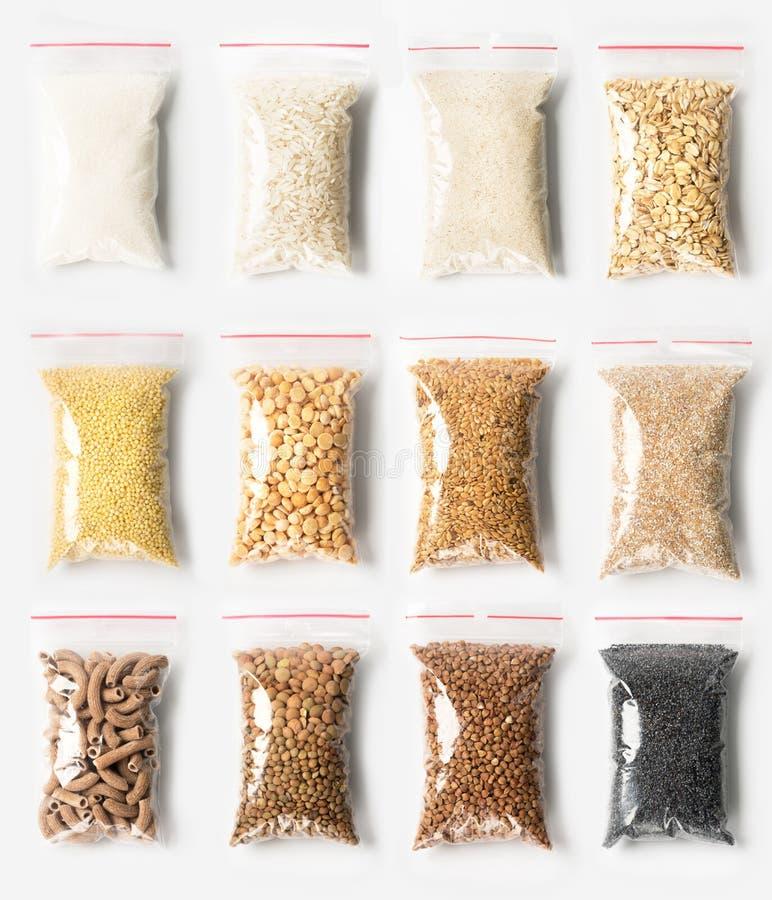 Set Plastikowy przejrzysty suwaczek zdojest z pełnym premii groats odizolowywający na białym, próżnia pakunki z makaronem, grochy obraz stock