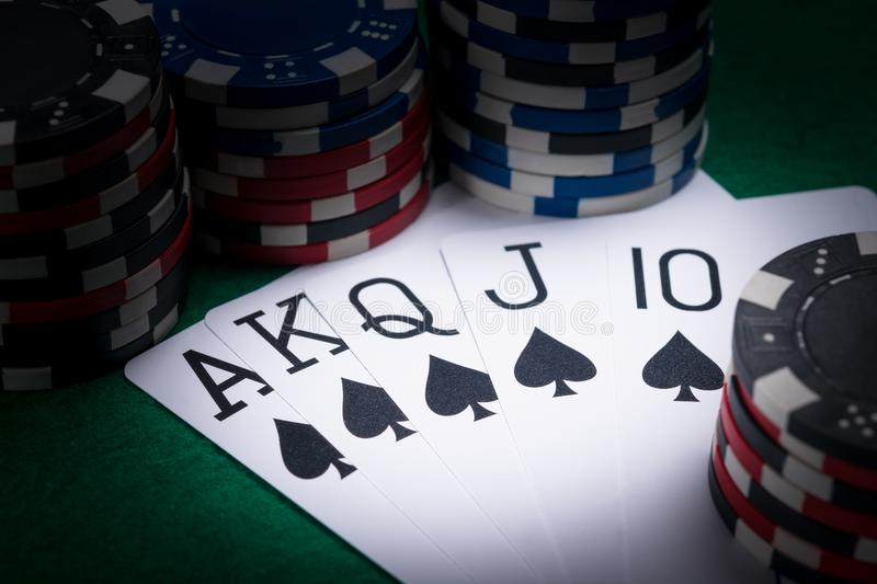 Set of poker cards with the best combination for a player in the dark of a casino royalty free stock image