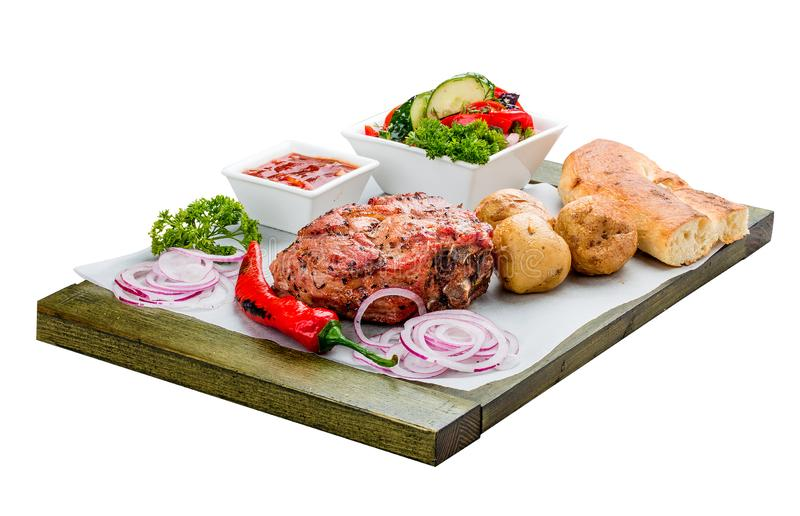 Set of pork steak, vegetable salad, potatoes and sauce. On a wooden board. Chalagach royalty free stock images
