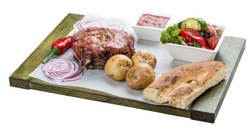 Set of pork steak, vegetable salad, potatoes and sauce. Chalagach. Set of pork steak, vegetable salad, potatoes and sauce. On a wooden board. Chalagach stock image