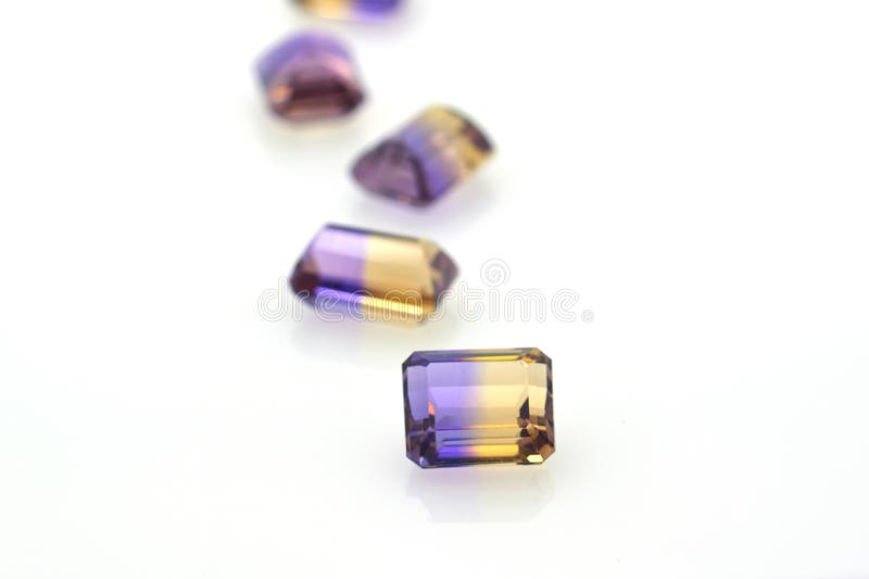 Set of precious purple and yellow polished gems of ametrine. Jewelry and precious stones. On white background stock photo