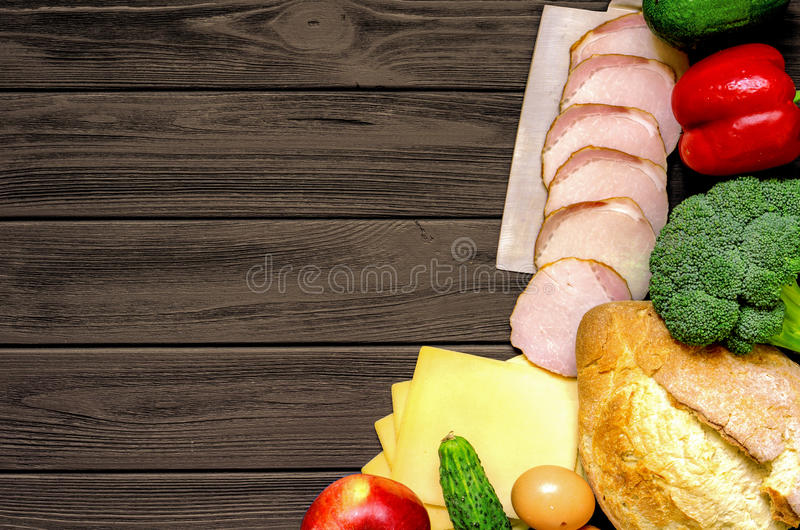 Set of products for cooking on brown vintage wooden work surface. Set of products for cooking - apple, bell pepper, cucumber, fresh bread, eggs, sliced ham stock image