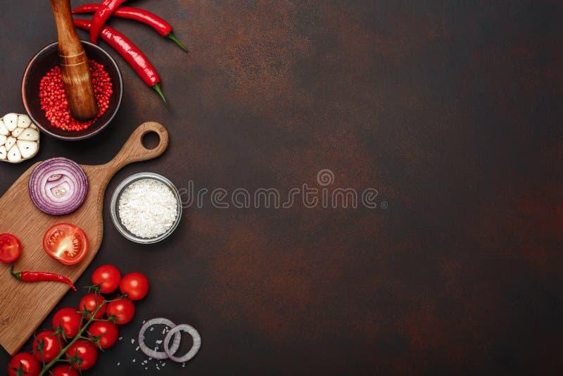 Set produkty na tnącej desce od czereśniowych pomidorów, rozmarynów, czosnku, czerwonego pieprzu, cebuli, soli i pikantności moźd fotografia royalty free