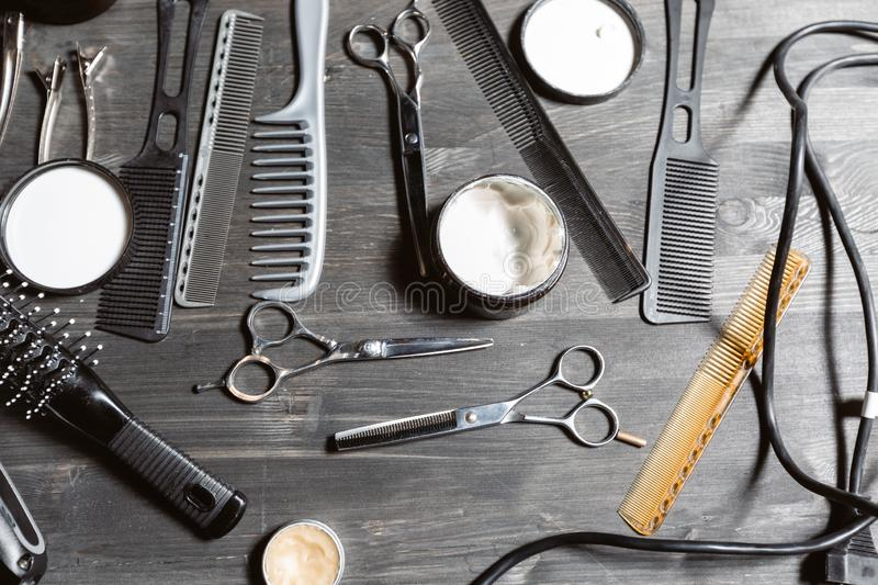 Set of professional hairdresser tools on grey background. Wooden table in barbershop. Working tool of barber master stock images