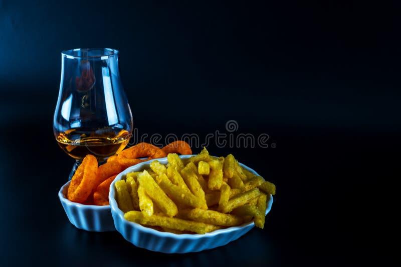 Set przekąski z różnymi upadami i pojedynczy słód w szkle, fotografia stock