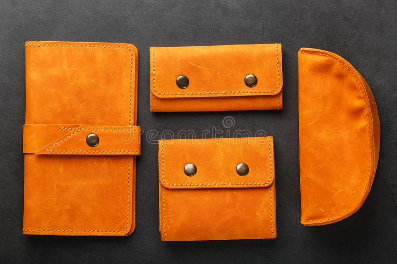 A set of purse, bag, partman, case for glasses and a key holder, made of genuine leather Nubuck on a dark background. Elements of leather craft products stock images
