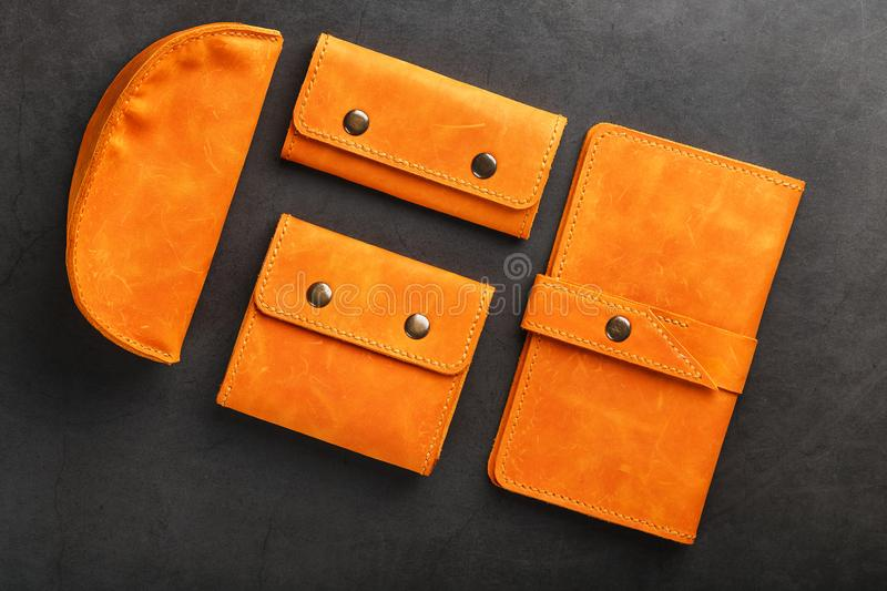 A set of purse, bag, partman, case for glasses and a key holder, made of genuine leather Nubuck on a dark background. Elements of leather craft products royalty free stock photography
