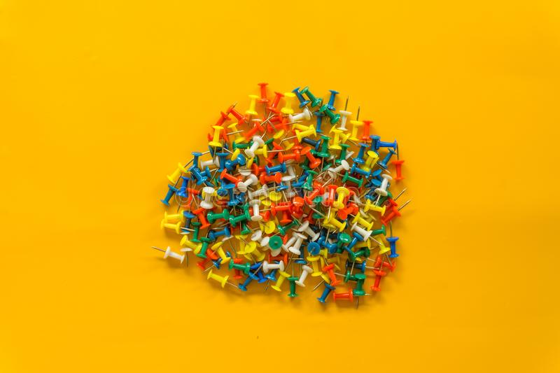 Set of push pins in different colors. Thumbtacks. Top view. on Yellow background royalty free stock photos