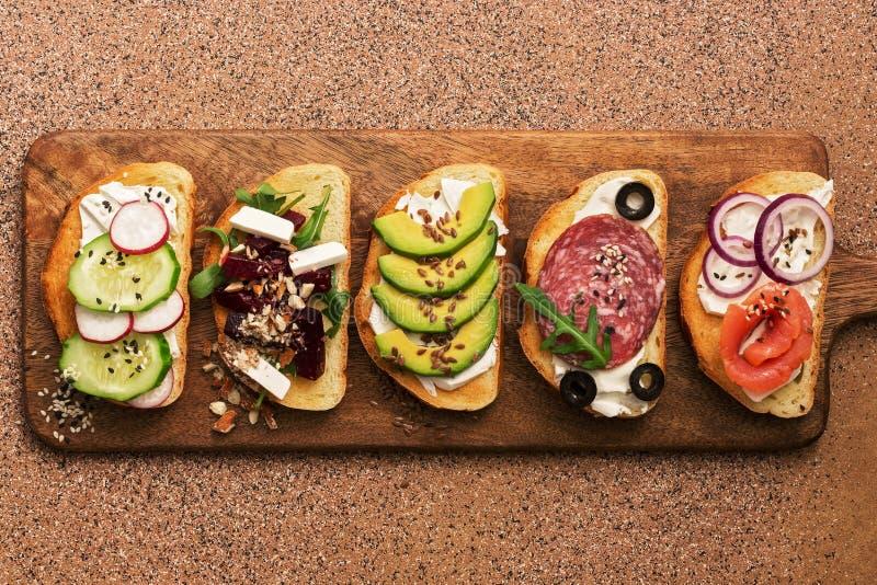 Set różnorodność grzanka z łososiem, kiełbasą, avocado, burakiem, feta serem, ogórkiem i rzodkwią na tnącej desce, Odgórny widok zdjęcie stock