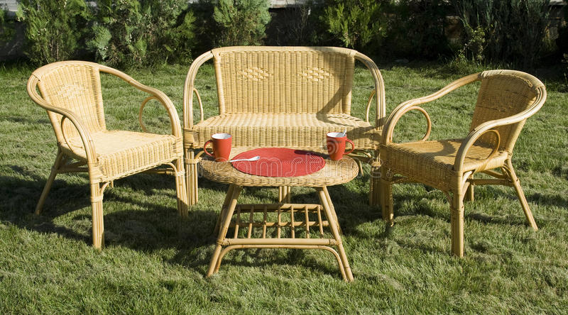 Set of rattan furniture on green grass in the yard. Set of rattan furniture with armchairs, two seater sofa and table on green grass in the yard stock photo