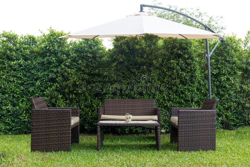 Set of rattan garden furniture under a big garden umbrella stock photos