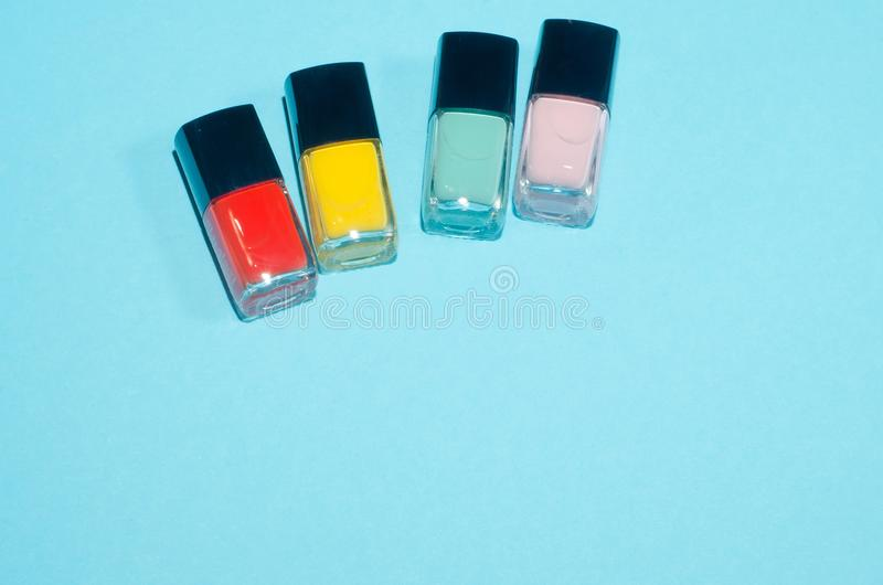 Set of red, pink, green and yellow. nail polish. Make up beauty products on blue background. Decorative cosmetics. Top view, flatl royalty free stock photography