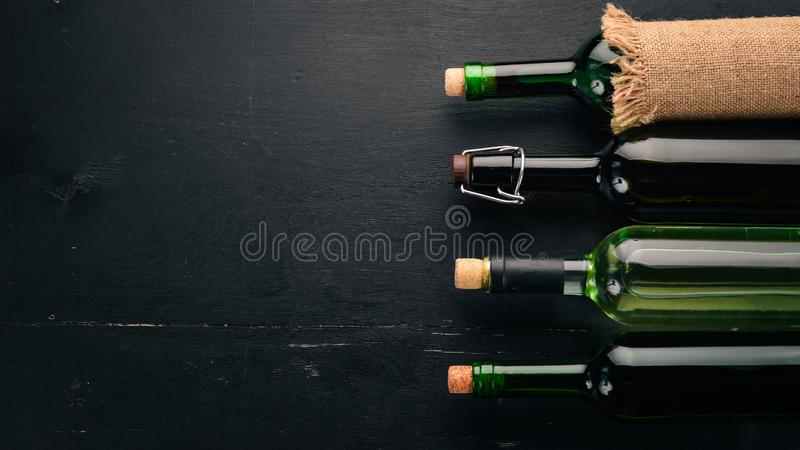 Set of red and white wine in bottles and glasses. Grape. On a black wooden background. Free space for text. royalty free stock image