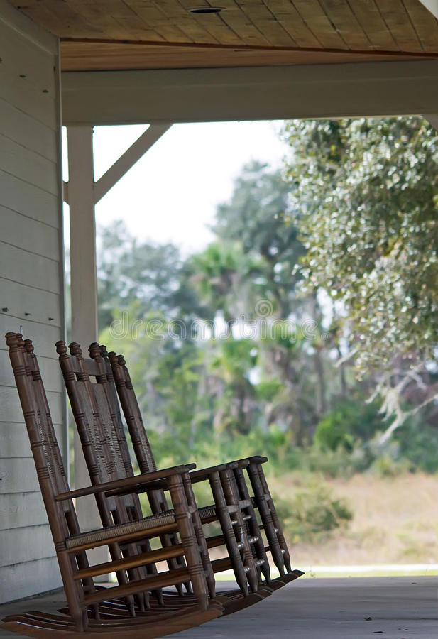 A set of rocking chairs. Several rocking chairs on a front porch in an old Florida home stock photos