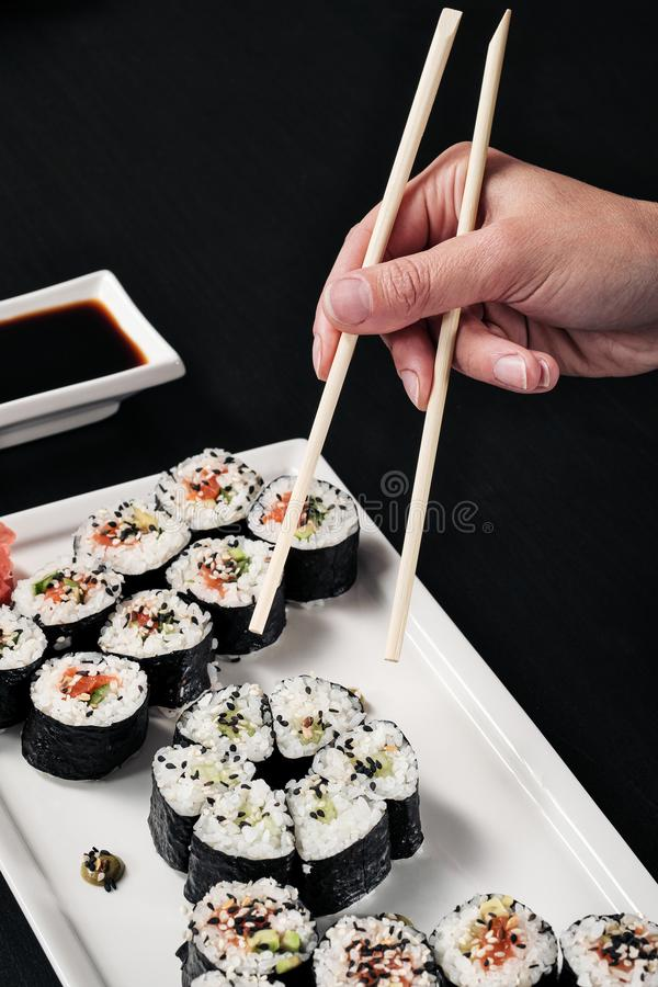 Set of rolls with red fish and ginger. Table setting. Black background. Ingredients for cooking Japanese cuisine. stock images
