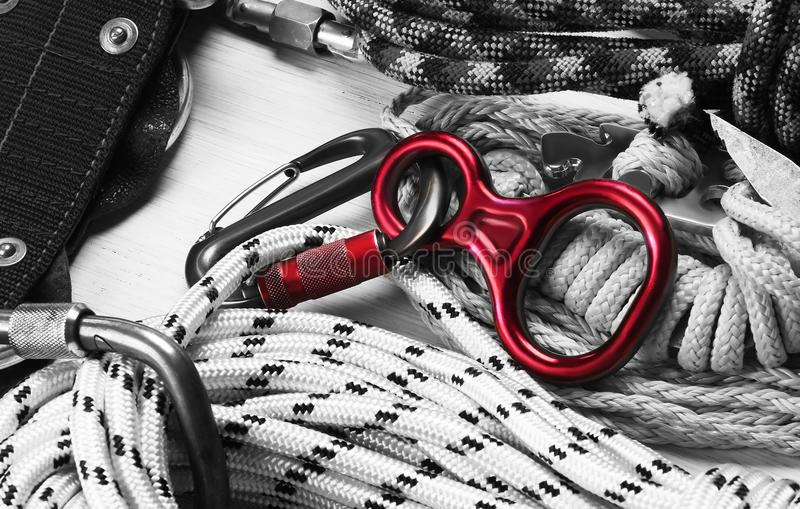 Set of ropes and carabiners for rock climbing. Color in black and white. red equipment for descent. royalty free stock image