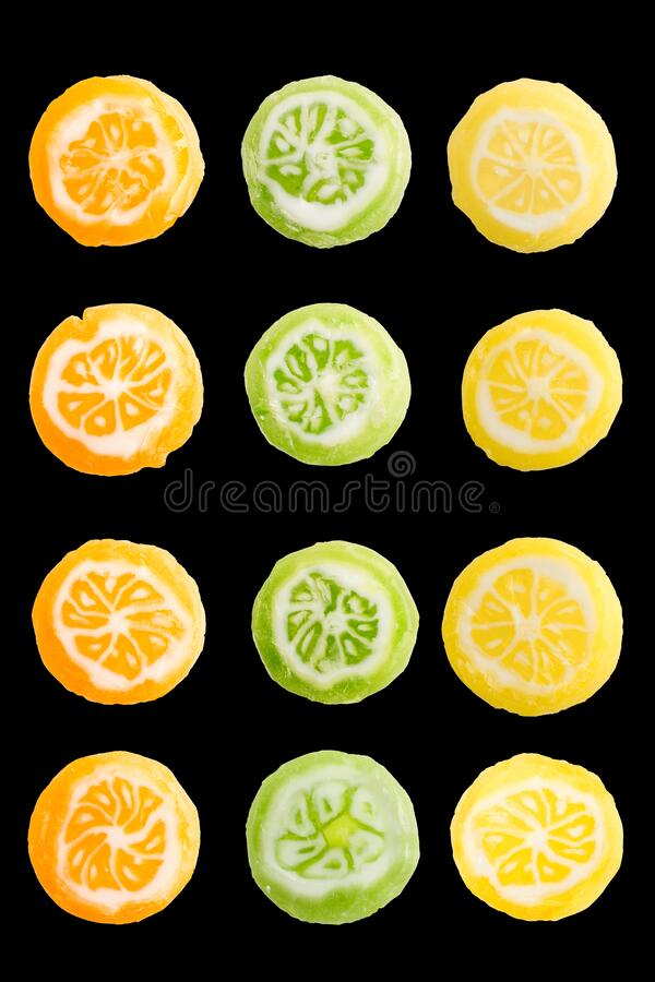 Set of round, small, multi-colored caramel candies in form of citrus slices. Isolated on black background. Sweeties.  stock image