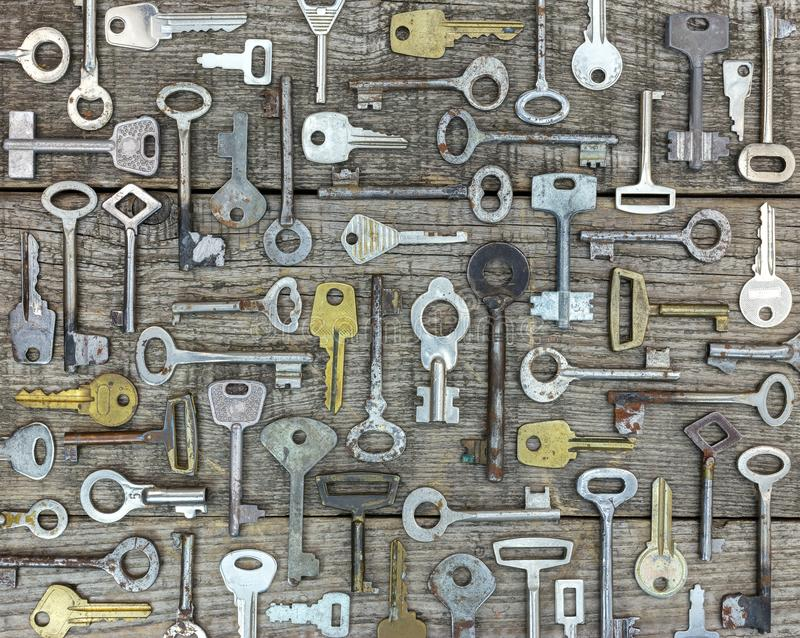 Set of rusty old keys on gray wooden rustic boards stock photo