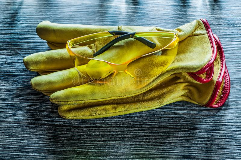 Set of safety gloves glasses on wooden board stock images