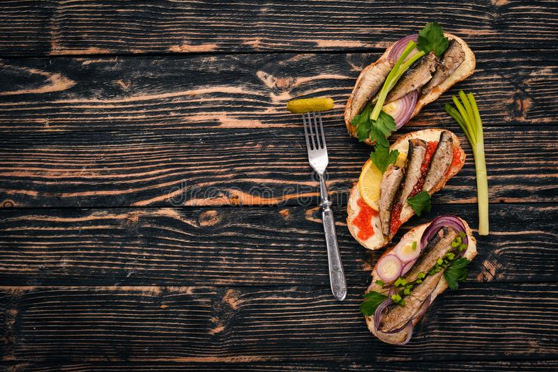 A set of sandwiches with sprats, and caviar, onion and parsley, on a wooden background. Top view. Copy space stock photos