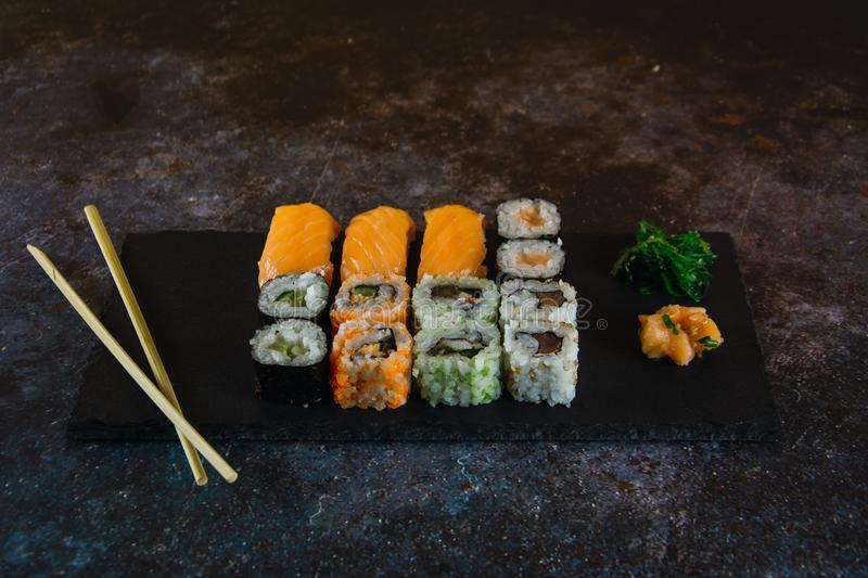 Set of sashimi sushi and sushi rolls served on stone slate accompanied with traditional soy sauce and seaweed stock image