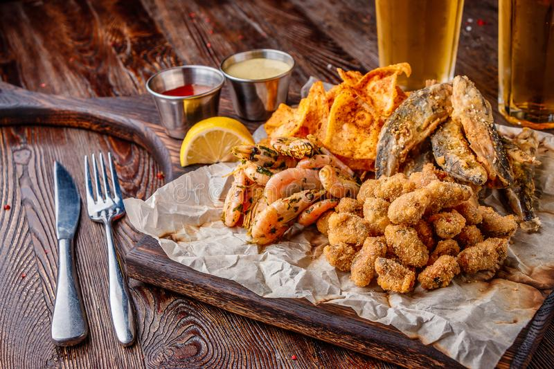 Set seafood: mussels, shrimps, small fried sea fish and crackers, food that is usually served with beer, horizontal orientation. Close up royalty free stock photos