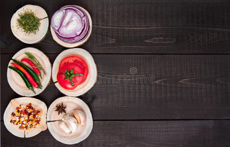Set of seasonings and spices on wooden brown background with tomato, onion. garlic, pepper stock image