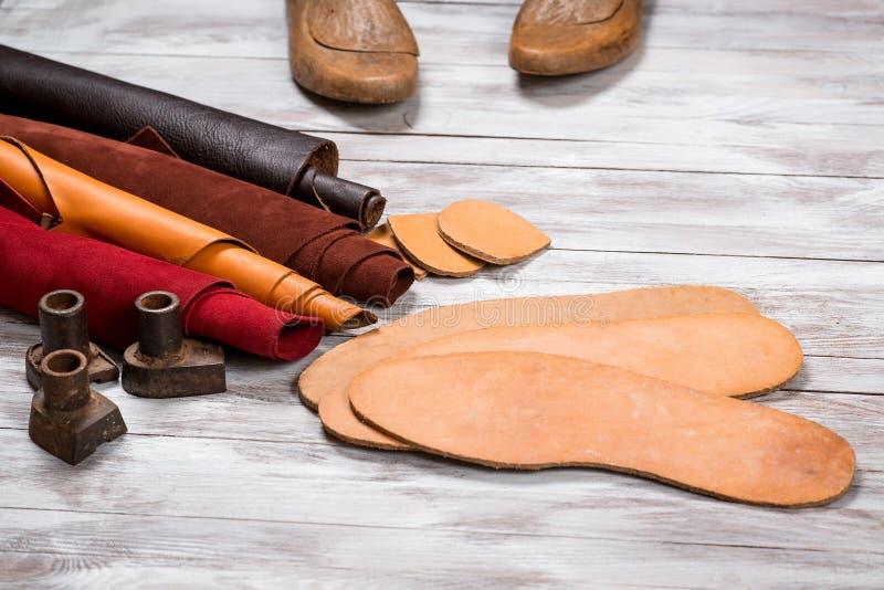 Set skóra w rolkach, rzemioseł narzędzia na białym drewnianym tle Miejsce pracy dla szewc Pracujący handmade narzędzia na praca s zdjęcia royalty free