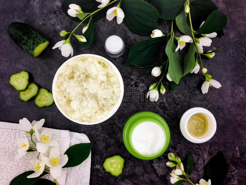 Set of spa treatment products on dark stone background. Flat lay, top view. Set of spa treatment products: creme, scrub, decorated with jasmine flowers on dark stock photo