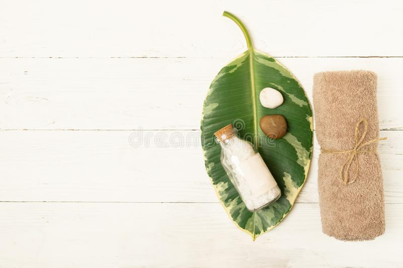 Set for spa treatments. Clean soft towels bath salts are stacked on leaf tropical green plant on a light background. stock photography