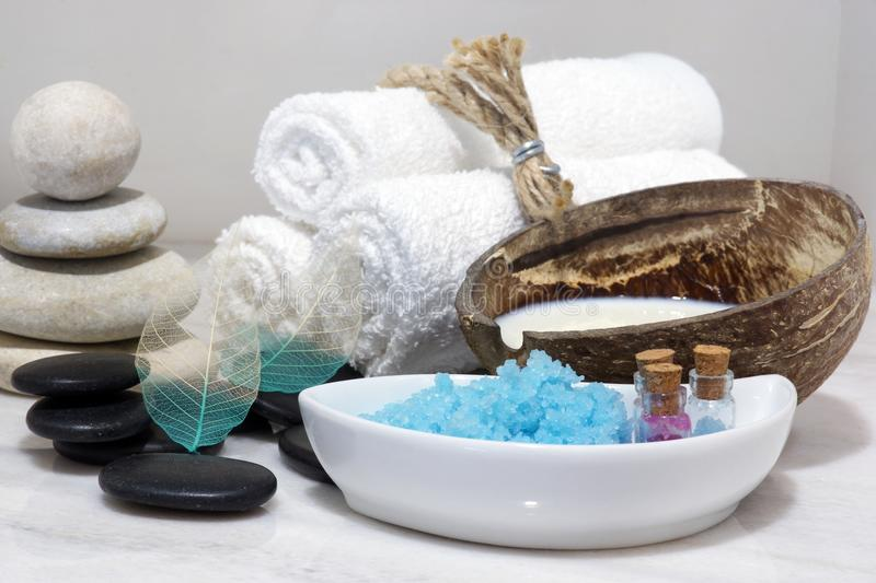 A set for Spa treatments with coconut milk, hot stones and blue bath salt is located on a white marble countertop. stock image