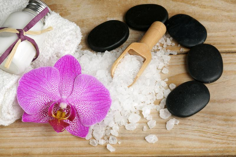 Set for spa treatments with lotions for skin, orchid flowers, bath salt and black stones for a hot massage on a wooden background stock photos