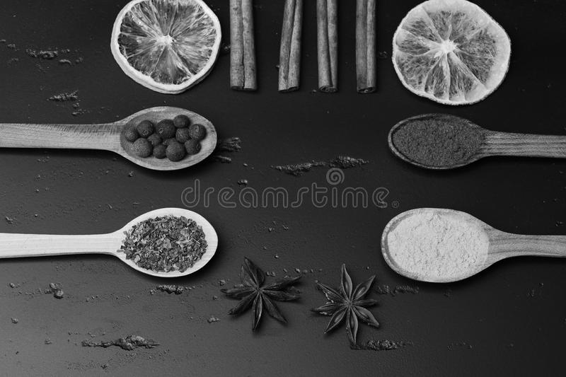 Set of spices on dark grey wood background. Food art concept. Wooden spoons with paprika, turmeric and herbs stock photos