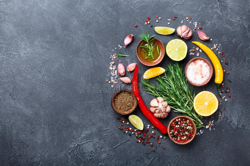 Set of spices and herbs on black stone table top view. Ingredients for cooking. Food background. stock photos