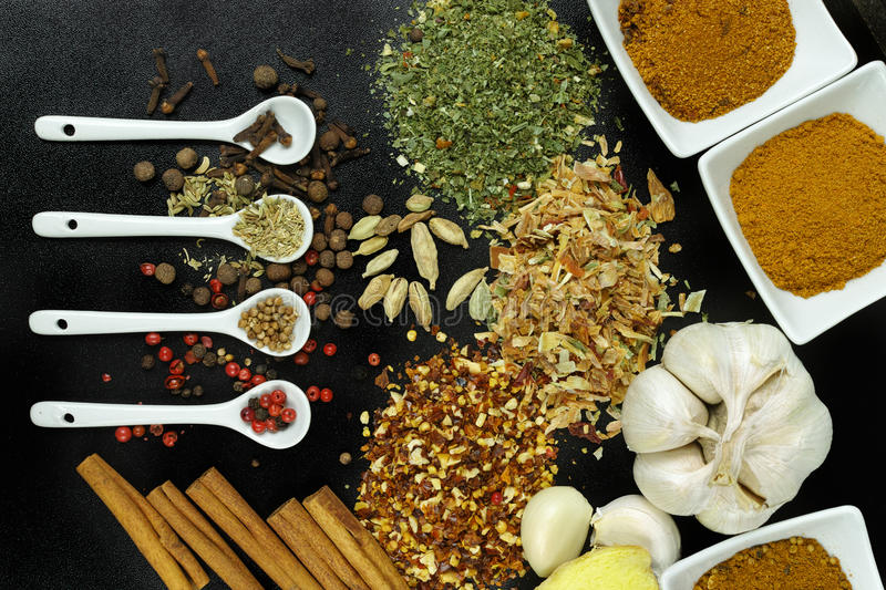 Set of spices and seasonings with white spoons on black stock photos