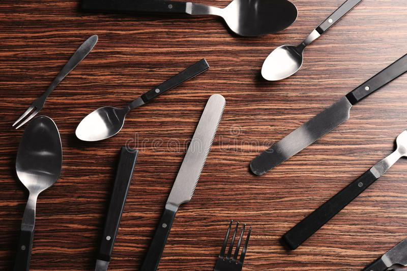 Set of spoons, forks and knives on wooden background royalty free stock photography
