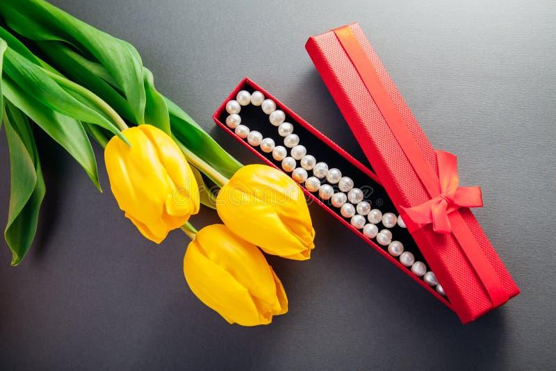 Set srebro kolczyki z perłami w prezenta pudełku z żółtymi tulipanami i pierścionek Teraźniejszość dla Macierzystego ` s dnia zdjęcia royalty free