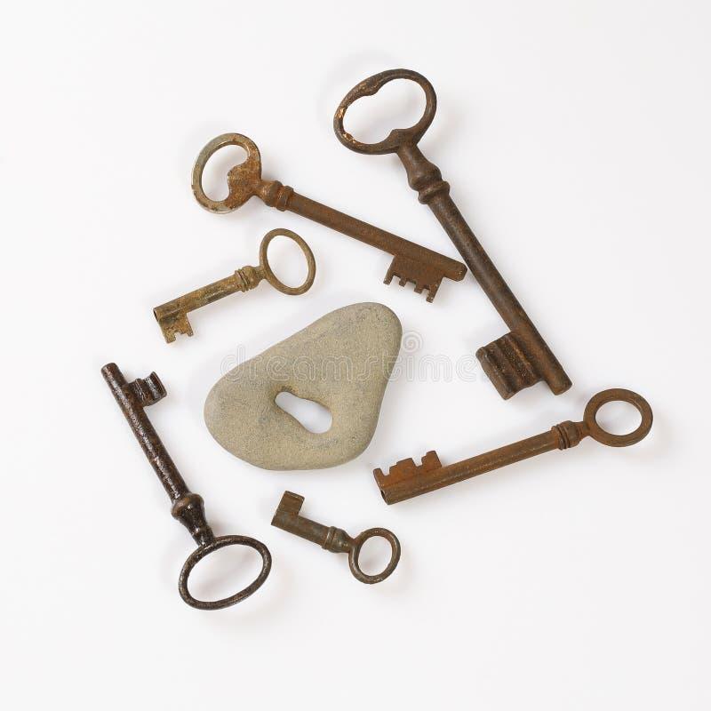 Set starzy ośniedziali klucze umieszczający wokoło popielatego kamienia z kluczową dziurą na białym tle obraz royalty free