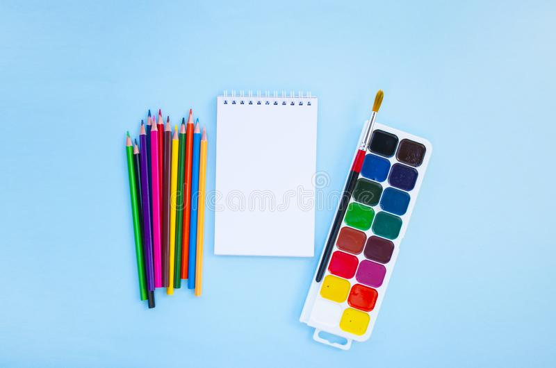 Set of stationery. Back to school concept. Colorful pencils, notebook, paint brush and watercolors on blue background with copyspace. Flat lay style. Back to royalty free stock images