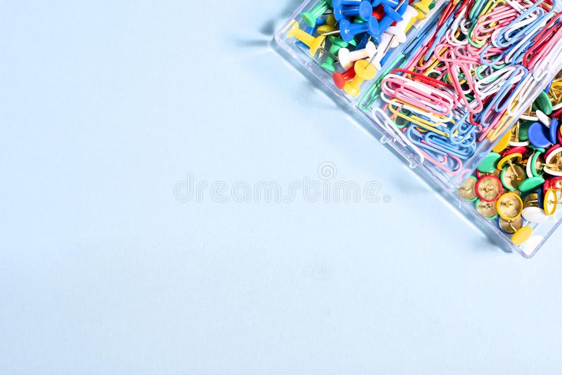 A set of stationery made of multi-colored buttons and paper clips in a box on. A blue surface royalty free stock photos