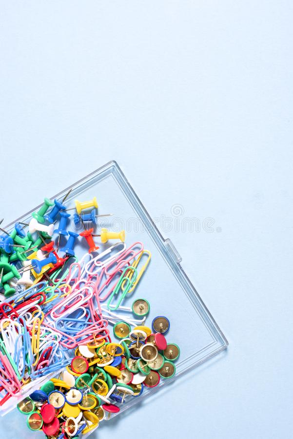 A set of stationery made of multi-colored buttons and paper clips in a box on. A blue surface royalty free stock image