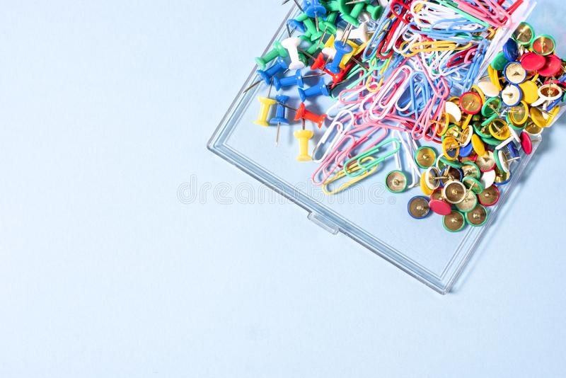 A set of stationery made of multi-colored buttons and paper clips in a box on. A blue surface stock photos