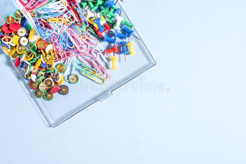 A set of stationery made of multi-colored buttons and paper clips in a box on. A blue surface royalty free stock images
