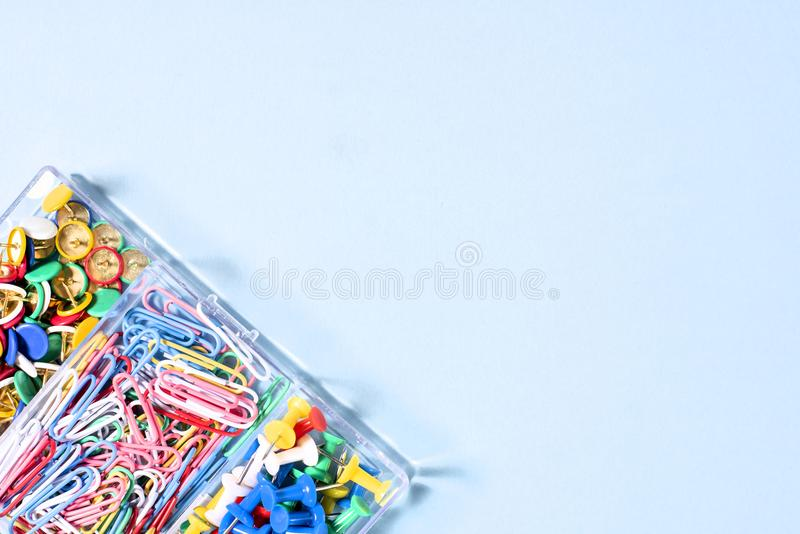 A set of stationery made of multi-colored buttons and paper clips in a box on. A blue surface stock photo