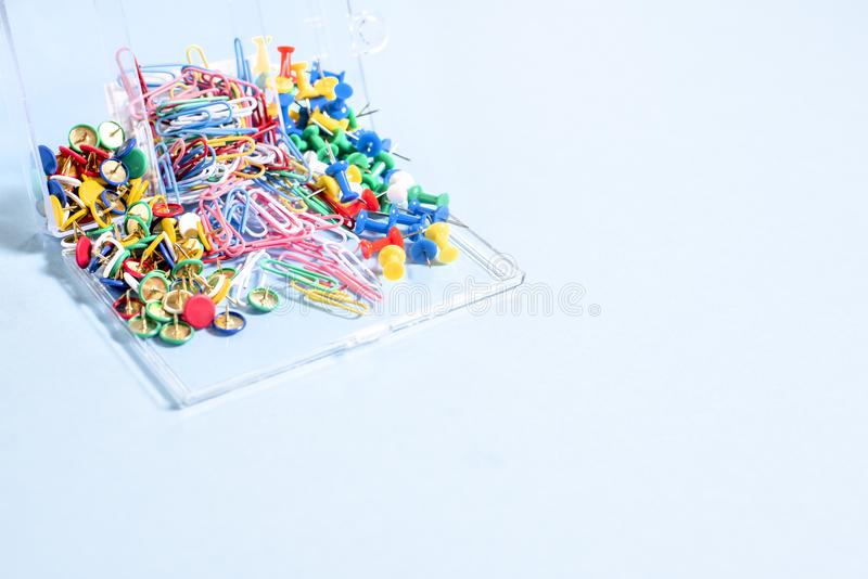 A set of stationery made of multi-colored buttons and paper clips in a box on. A blue surface stock photography