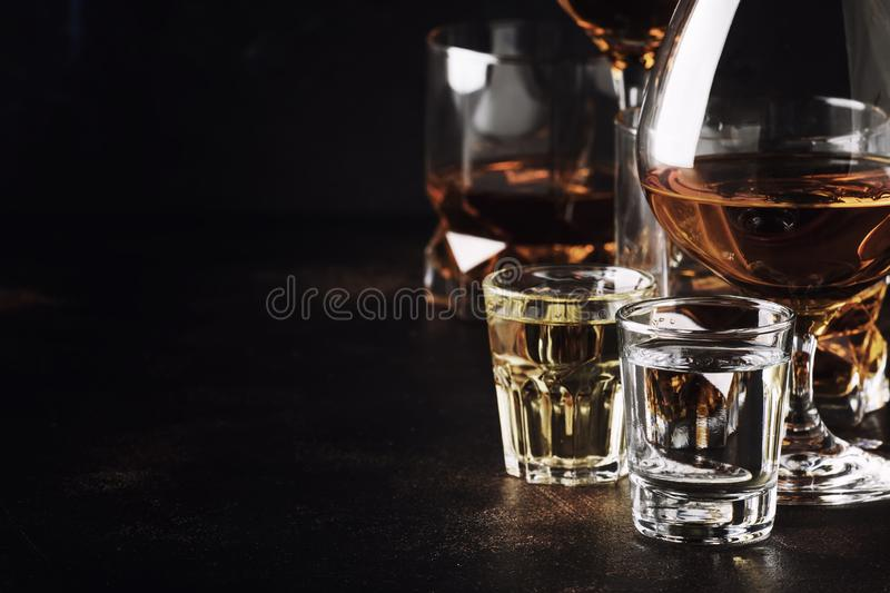 Set of strong alcoholic drinks in glasses and shot glass in assortent: vodka, rum, cognac, tequila, brandy and whiskey. Dark stock photography
