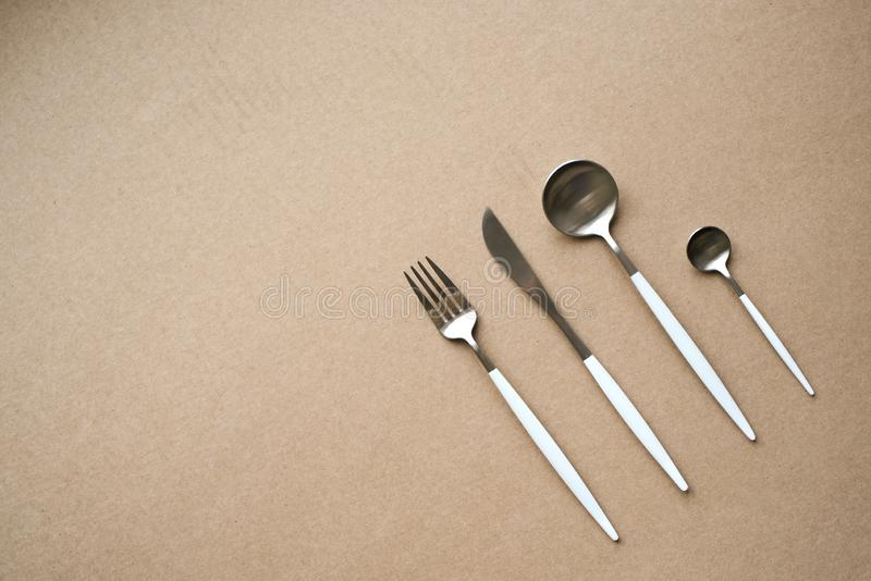 White and chrome cutlery. Set of stylish white and chrome cutlery on beige background, top view, copy space. Table set, menu design stock photography