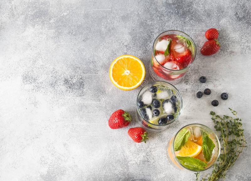 Set of summer healthy cocktails, various citrus infused waters, lemonades or mojitos, with lime and blueberries, orange and strawb royalty free stock photography