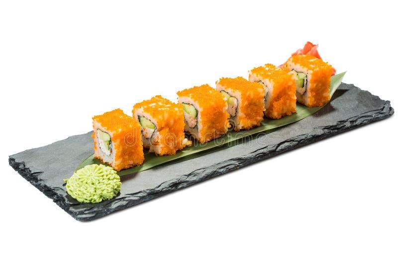 Set of sushi on black slate substrate, isolated. Set of sushi on a black substrate, isolated on white background royalty free stock photos