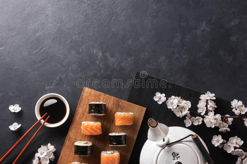 Set of sushi and maki rolls with branch of white flowers and teapot with the inscription green tea on stone table royalty free stock photo